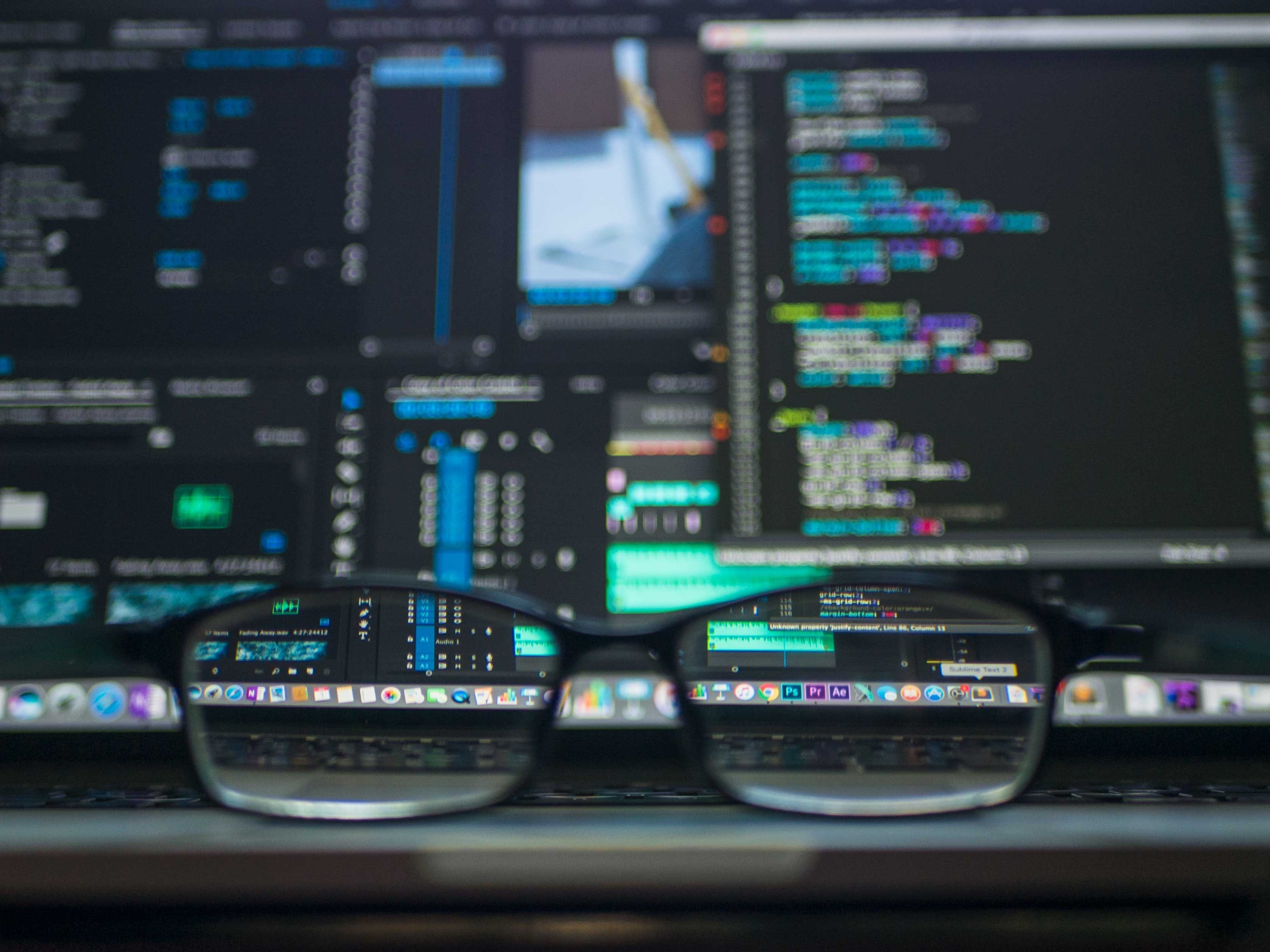 A pair of glasses in front of a computer with coding on the screen