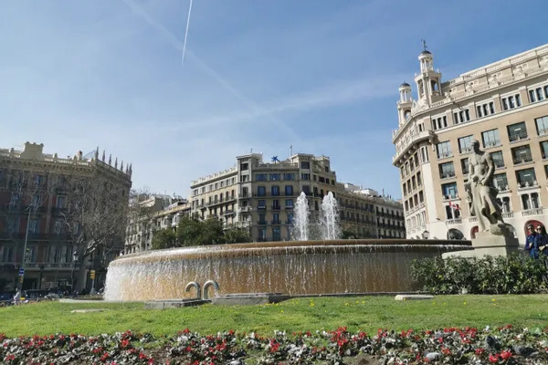 A photo of Plaça de Catalunya, Barcelona, looking from a low angle towards a blue sky with airplane trails